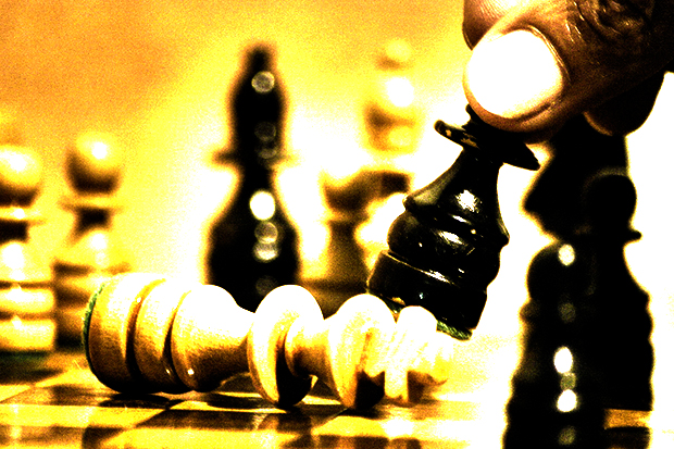 Picture of chess board, king lying down, a hand moving another piece. Hot off the chess, classic game.
