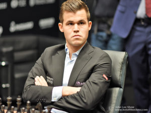 Magnus Carlsen, sitting with his arms folded, ready to start game 1. Photograph by John Lee Shaw © www.hotoffthechess.com.